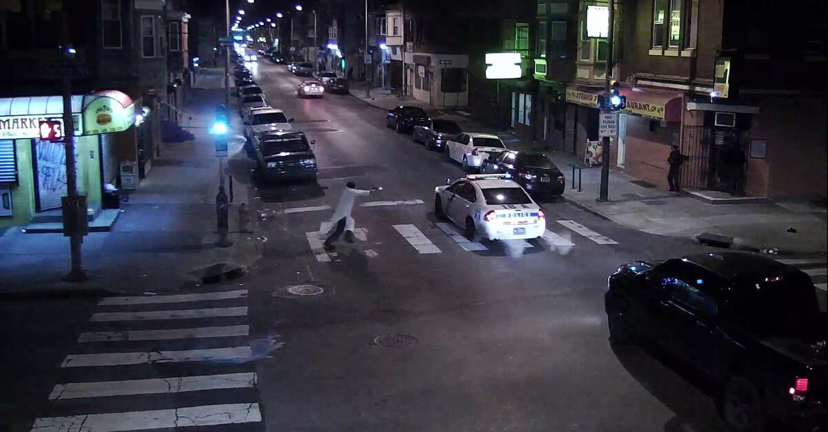 In this frame from a Thursday, Jan. 7, 2016 video provided by the Philadelphia Police Department, Edward Archer runs with a gun toward a police car driven by Officer Jesse Hartnett in Philadelphia. Archer, using a gun stolen from police, said he was acting in the name of Islam when he ambushed Hartnett sitting in his marked cruiser at an intersection, firing shots at point-blank range, authorities said. (Philadelphia Police Department via AP) ORG XMIT: NY201