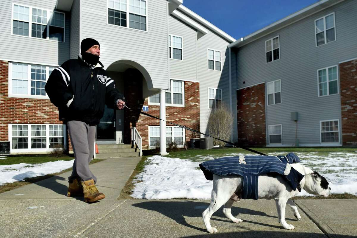 Tenant Chris Torre takes his Boston terrier, Raider, for a walk on Wednesday, Jan. 6, 2016, at Bridgewater Apartments in Milton, N.Y. (Cindy Schultz / Times Union)