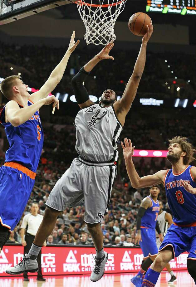 LaMarcus Aldridge goes between Kristaps Porzingis and Robin Lopez to score as the Spurs host the Knicks at the AT&T Center on January 8, 2016. Photo: TOM REEL, STAFF / SAN ANTONIO EXPRESS-NEWS / 2016 SAN ANTONIO EXPRESS-NEWS
