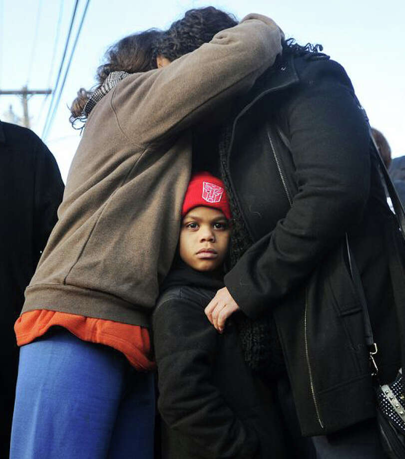 Neighbors hug after escaping a fire that ravaged a Bridgeport condominium, which left about 120 people homeless on the morning of New Year's Eve. Photo: Brian A. Pounds / Brian A. Pounds / Fairfield Citizen
