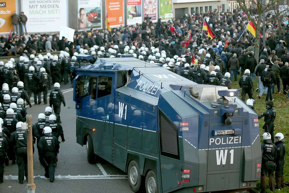 Police gather next to a water cannon in Cologne as they move to clear anti-Islam demonstrators. Photo: Oliver Berg, AFP / Getty Images