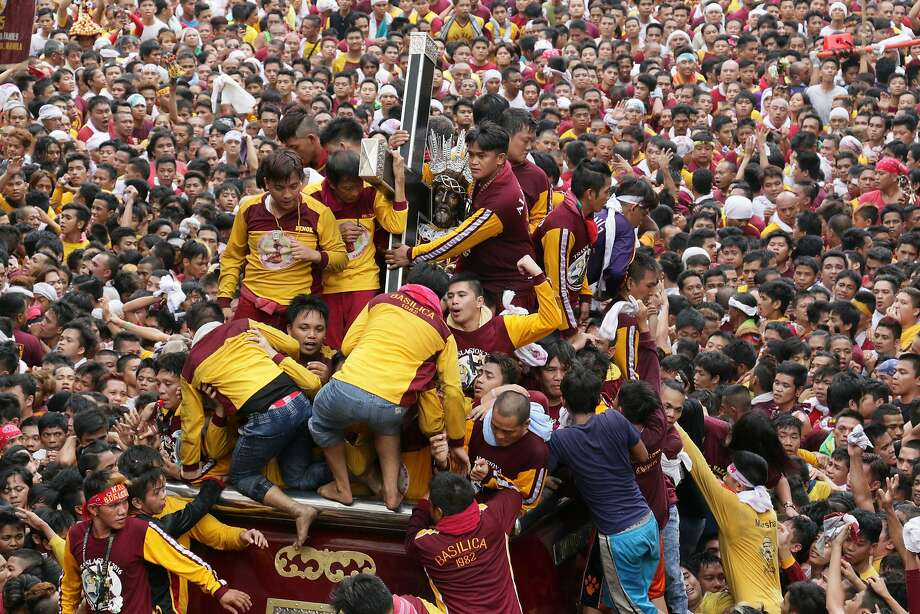 Devotees join the annual procession with the religious icon of the Black Nazarene in Manila. Participants in search of miracles hurl themselves to touch the centuries-old icon of Jesus. Photo: Joseph Agcaoili, AFP / Getty Images