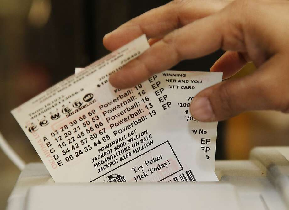 A merchant pulls Powerball lottery tickets from the printer at her store in Oklahoma City. Photo: Sue Ogrocki, Associated Press