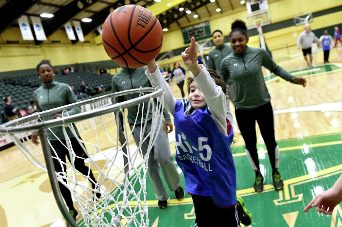 James Ellenberger, 7, of Ballston Spa, center, shoots for the low basket during the annual Hi-5 Sports basketball game against the Siena women's team on Saturday, Jan. 9, 2016, at Siena College in Loudonville, N.Y. Hi-5 Sports offers sports training for children and adults with special needs in order to build self-esteem, confidence and friendships. (Cindy Schultz / Times Union)
