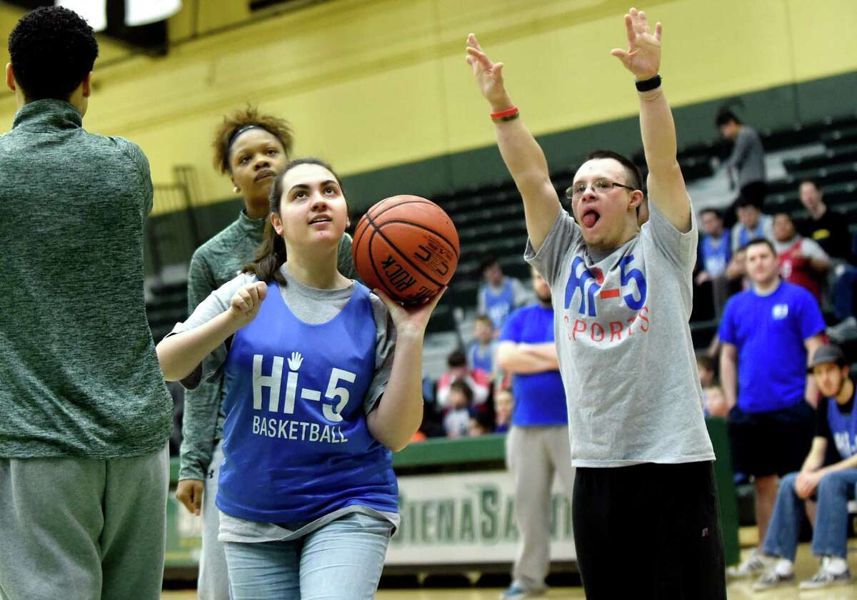 Adrienne Knoth, 21, of Delmar, center, shoots one handed and makes the basket as Bobby Batchelder, 21, lends support during the annual Hi-5 Sports basketball game against the Siena women's team on Saturday, Jan. 9, 2016, at Siena College in Loudonville, N.Y. Hi-5 Sports offers sports training for children and adults with special needs in order to build self-esteem, confidence and friendships. (Cindy Schultz / Times Union)