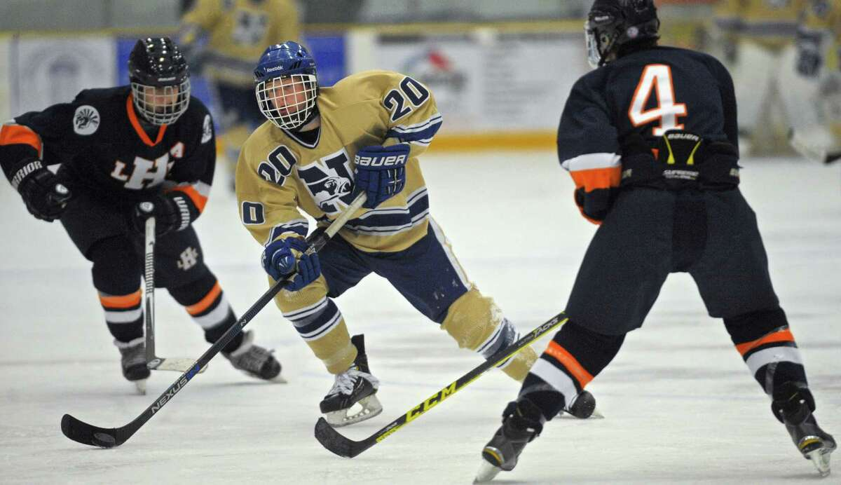 Newtown's Scott McLean (20) splits Lyman Hall's Hunter Boileau (8) and Chris Blanchard (4) in the boys hockey game between Lyman Hall/H-K/Coginchaug and Newtown, on Saturday, January 9, 2016, in the Danbury Ice Arena, in Danbury, Conn.
