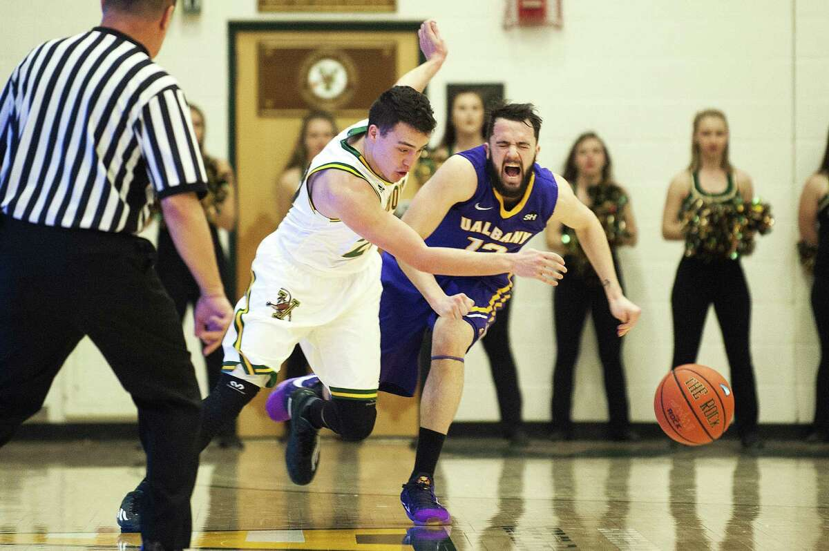 Catamounts Guard Ernie Duncan (20) steals the ball from Albany's Peter Hooley (12) during the men's basketball game between the Albany Great Danes and the Vermont Catamounts at Patrick Gym on Saturday afternoon January 9, 2016 in Burlington. (Brian Jenkins / Burlington Free Press)