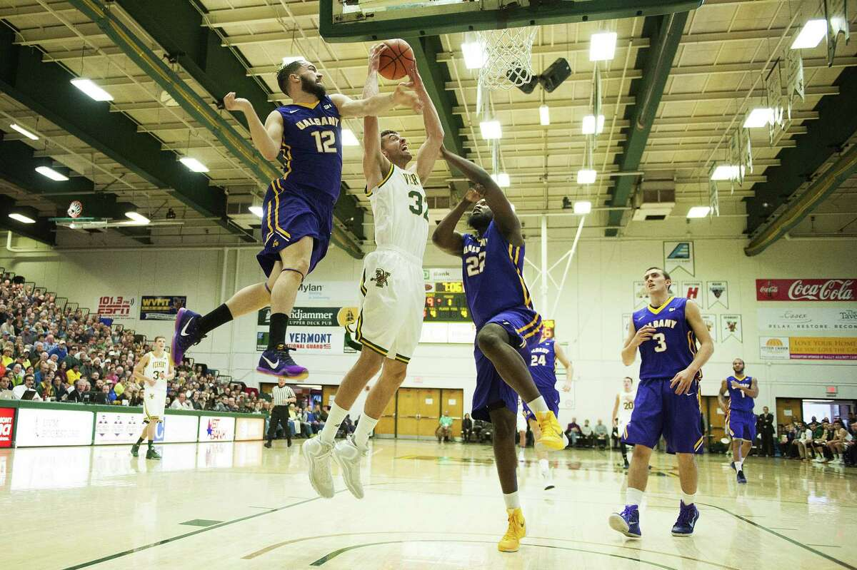 Catamounts Forward Ethan O'Day (32) leaps between Albany's Peter Hooley (12) and Richard Peters (22) for a lay up during the men's basketball game between the Albany Great Danes and the Vermont Catamounts at Patrick Gym on Saturday afternoon January 9, 2016 in Burlington. (Brian Jenkins / Burlington Free Press)