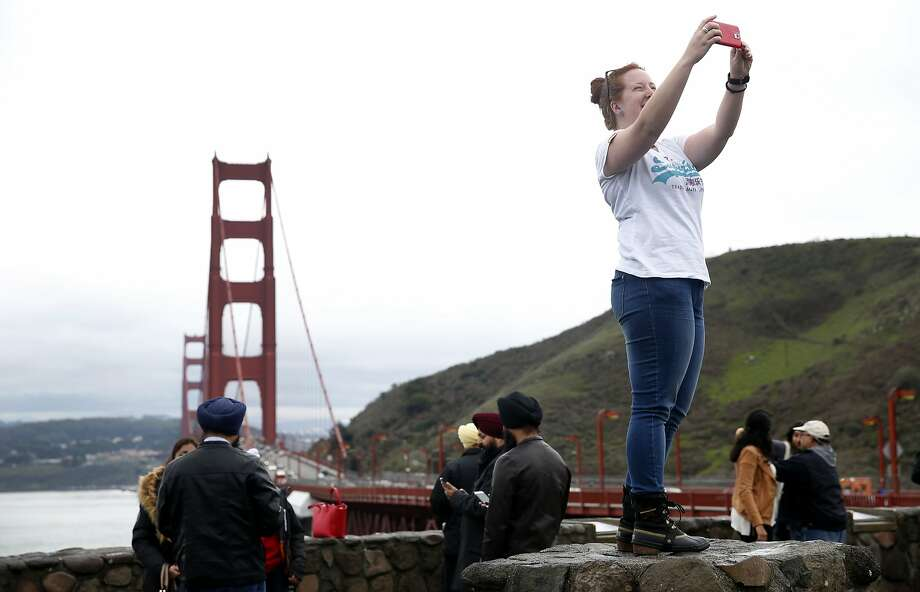 Visiting from Australia, Nicole Brown snaps a selfie from the north vista point of the Golden Gate Bridge in Sausalito, Calif. on Saturday, Jan. 9, 2016. During peak times, northbound traffic attempting to exit into the vista point's parking lot often backs up, creating significant congestion coming off the bridge. Photo: Paul Chinn, The Chronicle