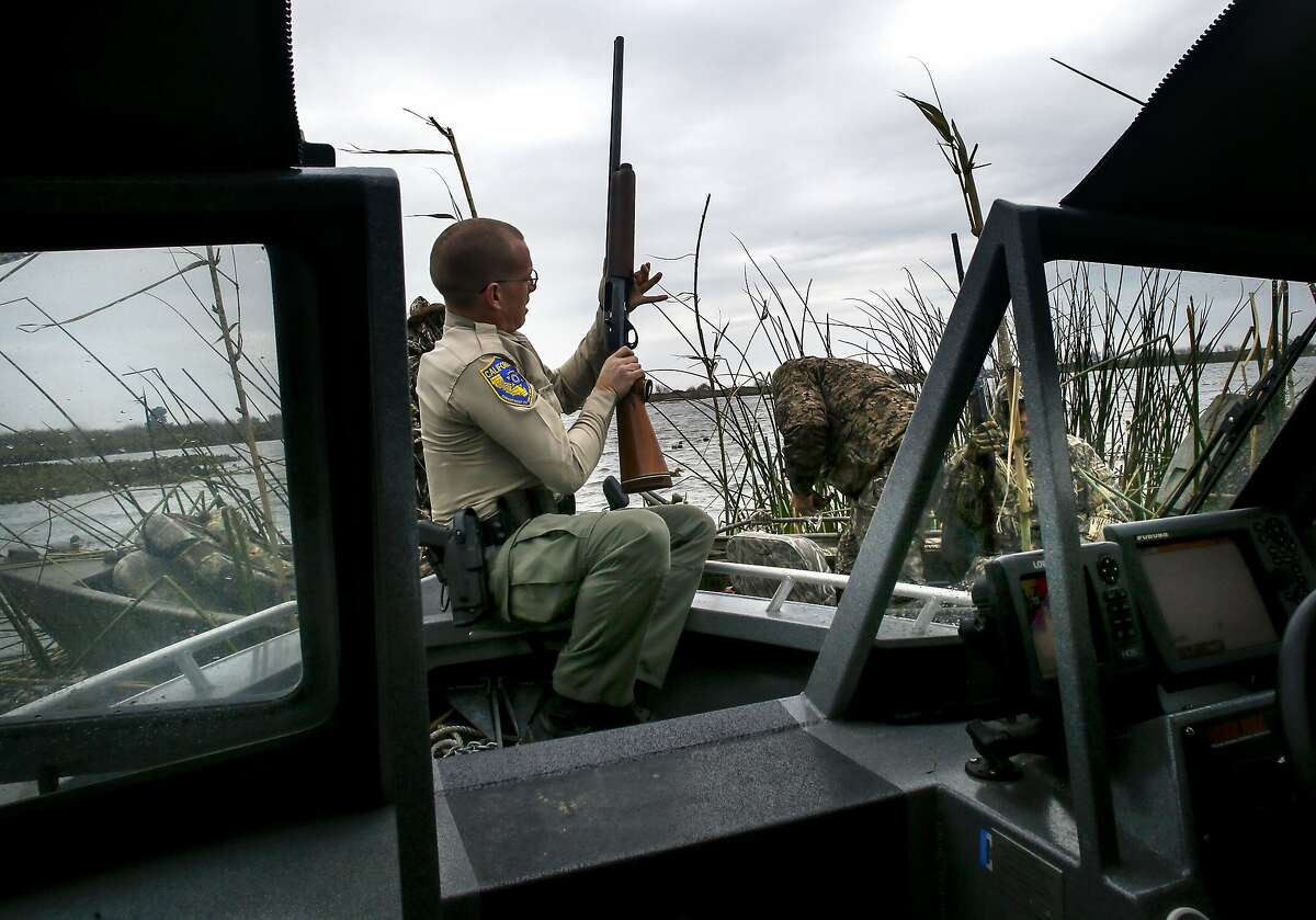 California Department of Fish and Wildlife Warden Ryan McCoy checks the shotguns of hunters during daily patrols on the California Delta near Brentwood, Calif. on Sat. January 9, 2016.