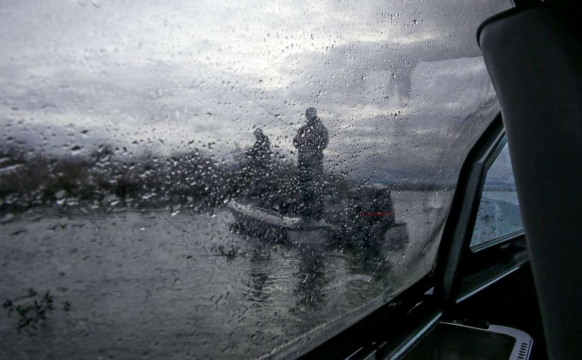 Fisherman are seen through the rainy windows of the boat operated by California Department of Fish and Wildlife Wardens Clint Garrett and Ryan McCoy during daily patrols on the California Delta near Brentwood, Calif. on Sat. January 9, 2016.