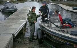 California Department of Fish and Wildlife Warden Clint Garrett checks fishing licenses at Orwood Marina during patrols on the California Delta near Brentwood, Calif. on Sat. January 9, 2016,