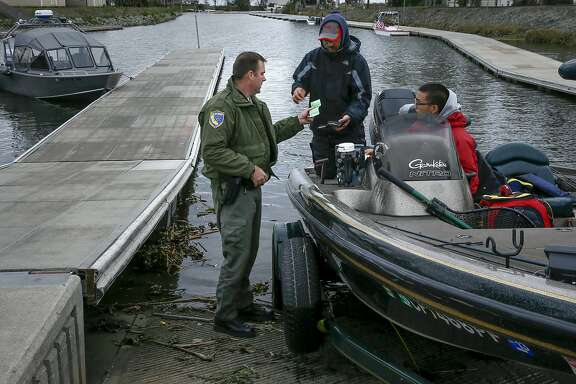 California Department of Fish and Wildlife Warden Clint Garrett checks fishing licenses at Orwood Marina during patrols on the California Delta near Brentwood, Calif. on Sat. January 9, 2016,
