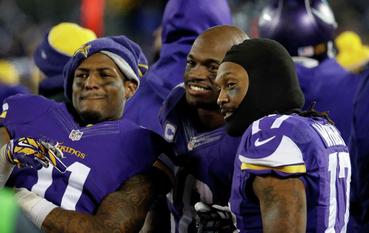 FILE - In this Dec. 27, 2015, file photo, Minnesota Vikings wide receiver Mike Wallace (11), running back Adrian Peterson (28) and wide receiver Jarius Wright (17) react on the sideline during the second half of an NFL football game against the New York Giants in Minneapolis. The Vikings hosted the Giants at the ninth-coldest game in their history. (AP Photo/Ann Heisenfelt, File) ORG XMIT: NY907