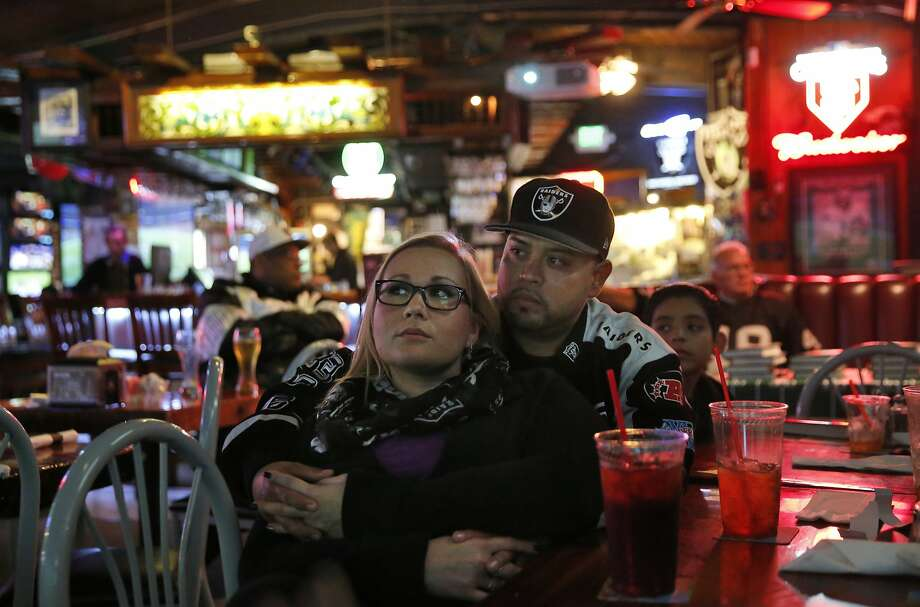 Raiders fans Beth Miller and Victor Arias watch the Kansas City vs. Houston Wild Card game at Ricky's Sports Theatre & Grill Jan. 9, 2015 in San Leandro, Calif. Photo: Leah Millis, The Chronicle