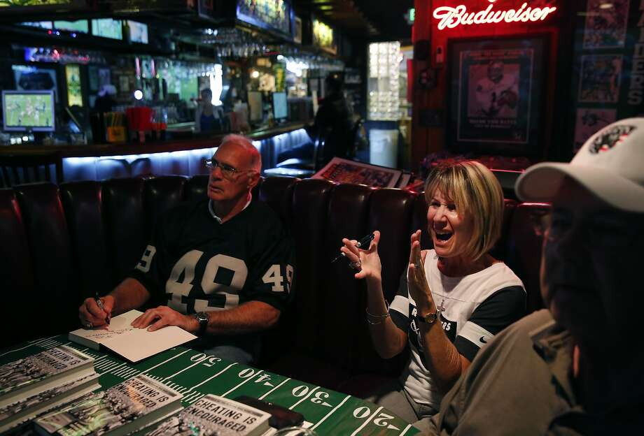 "Former Raiders player Mike Siani, left, Kristine Setting Clark and Mark Pinheiro watch the Kansas City vs. Houston Wild Card game as they also promote Siani and Clark's recent book ""Cheating is Encouraged"" at Ricky's Sports Theatre & Grill Jan. 9, 2015 in San Leandro, Calif. Photo: Leah Millis, The Chronicle"