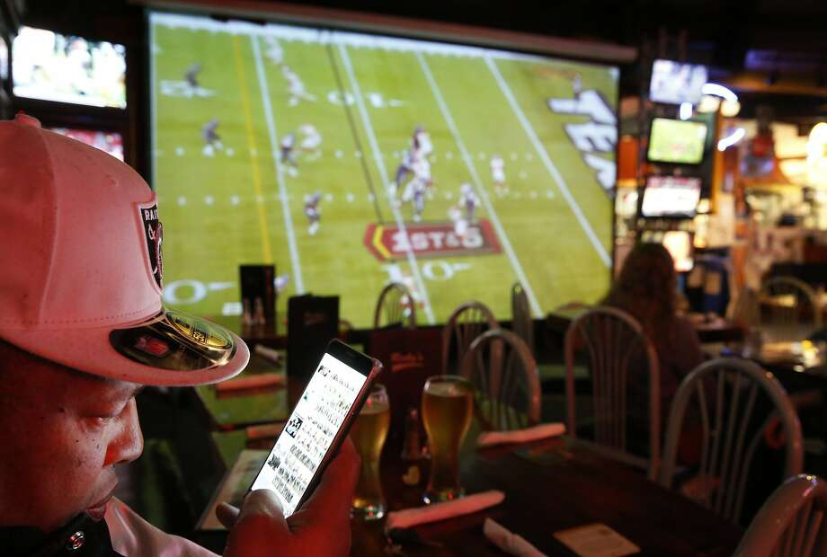 """Raiders fan James Davidson looks at hundreds of photos from various Raiders games from over the years as he watches the Kansas City vs. Houston Wild Card game at Ricky's Sports Theatre & Grill Jan. 9, 2015 in San Leandro, Calif. """"I hope they don't move."""" He said about his team. Photo: Leah Millis, The Chronicle"""