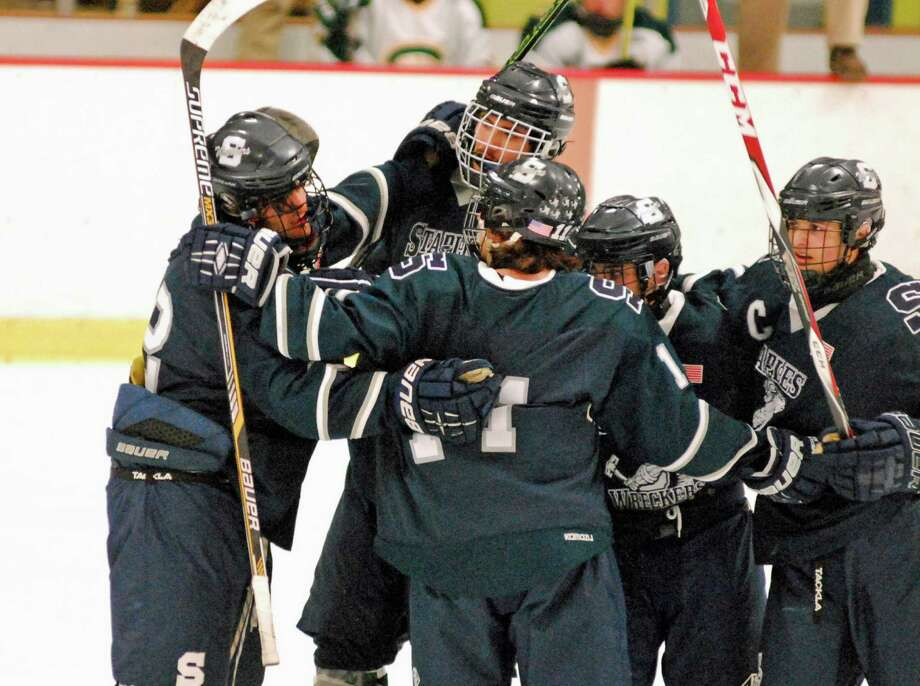 Staples' Ian Offenberg, left, celebrates with his teammates after he scored a goal against Trinity Catholic on Saturday, January 9th, 2016 at Terry Conners Rink in Stamford, Connecticut. Photo: Ryan Lacey/Staff Photo / Westport News Contributed
