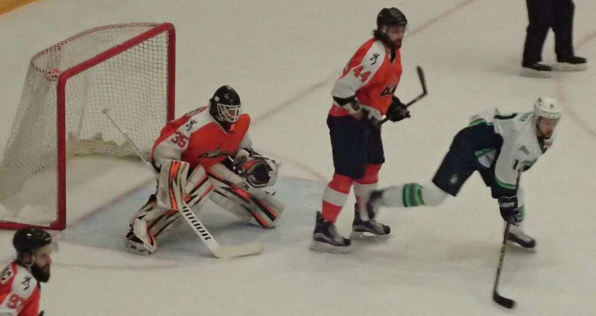 The Danbury Titans' Dean Yakura, right, takes a shove from the the Danville Dashers' Nathan Judd-Warren in front of Danville goalie Matt Anthony during their Federal Hockey League game at the Danbury Arena Jan. 9, 2016.