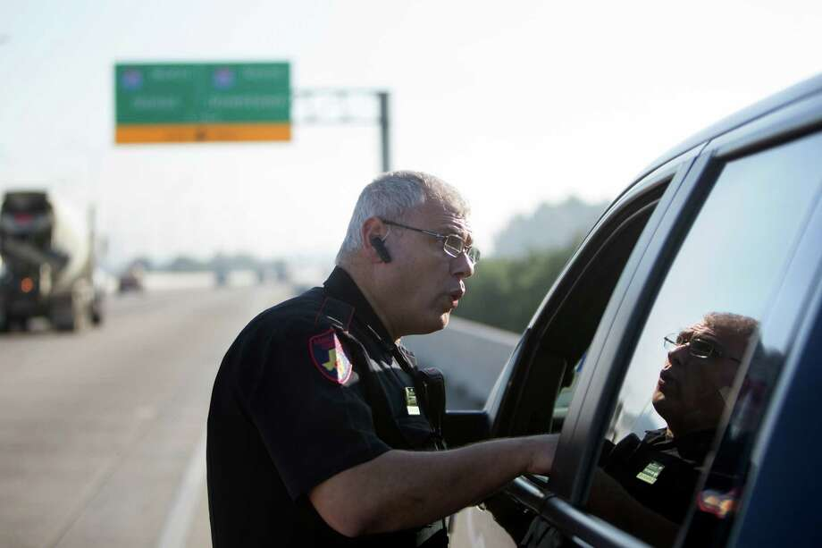 Harris County Constable, Precint 4 Lieutenant D. Fragkias talks to a driver before issuing a citation along the Sam Houston Tollway eastbound near I-45, Tuesday, Dec. 8, 2015, in Houston. The Harris County Toll Road Authority issued citations to prohibited vehicles due to unpaid tolls. Photo: Cody Duty /Houston Chronicle / © 2015 Houston Chronicle