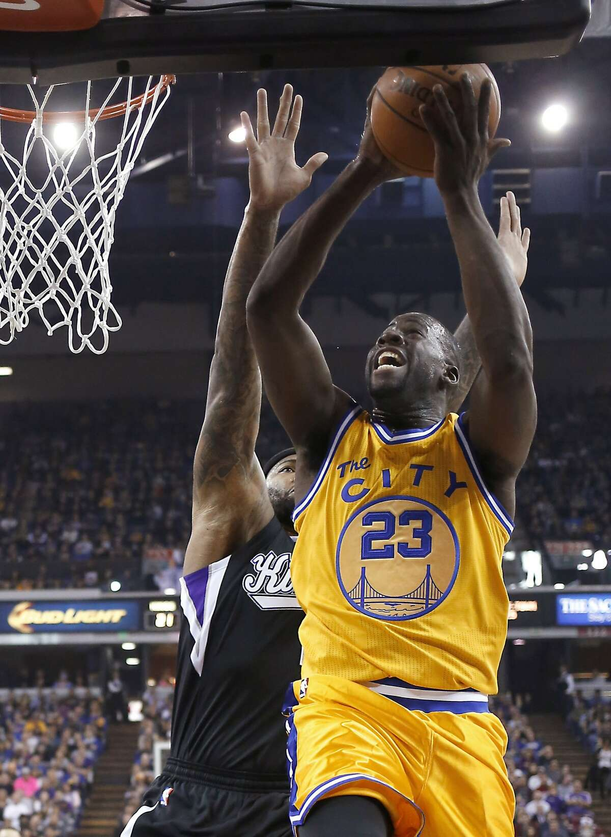 Golden State Warriors forward Draymond Green, right, goes to the basket against Sacramento Kings forward DeMarcus Cousins during the first quarter of an NBA basketball game Saturday, Jan. 9, 2016, in Sacramento, Calif. (AP Photo/Rich Pedroncelli)