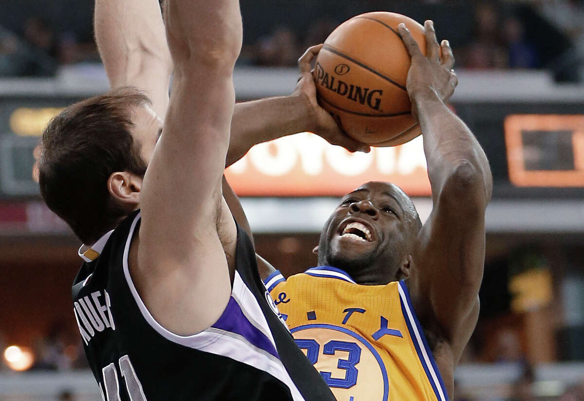 Warriors forward Draymond Green, right, goes to the basket against Sacramento Kings center Kosta Koufos during the first quarter of an NBA basketball game in Saturday, Jan. 9, 2016, in Sacramento, Calif.(AP Photo/Rich Pedroncelli)