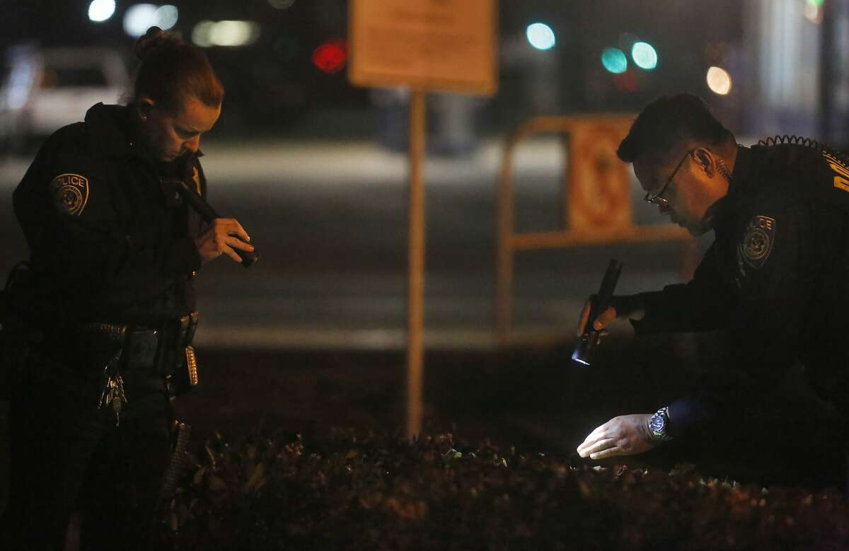 Police officers search the bushes near a bus stop on 7th Street outside of the West Oakland BART station, the closest stop where there was a fatal shooting on a BART train Jan. 9, 2015 in Oakland, Calif.