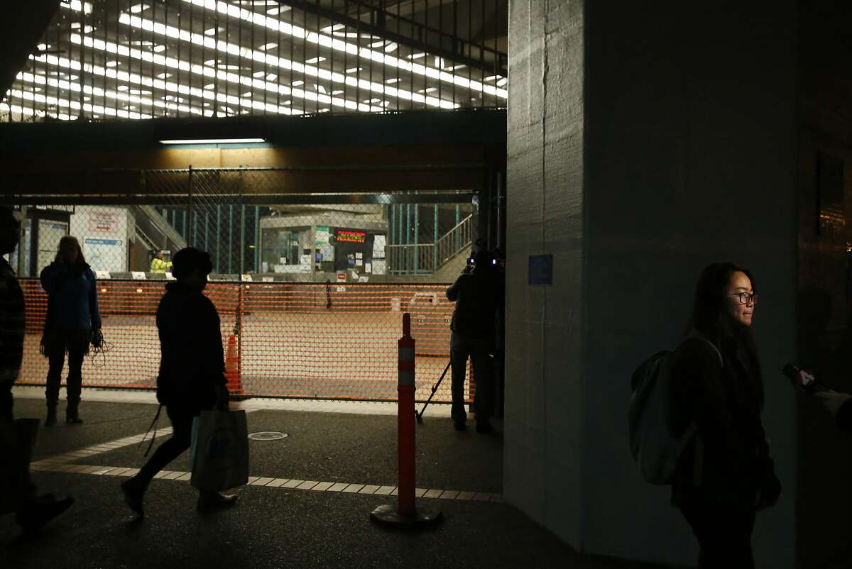 Witness Kelly Ching is interviewed by a television journalist outside of the closed West Oakland BART station, the closest stop where there was a fatal shooting on a BART train Jan. 9, 2015 in Oakland, Calif.