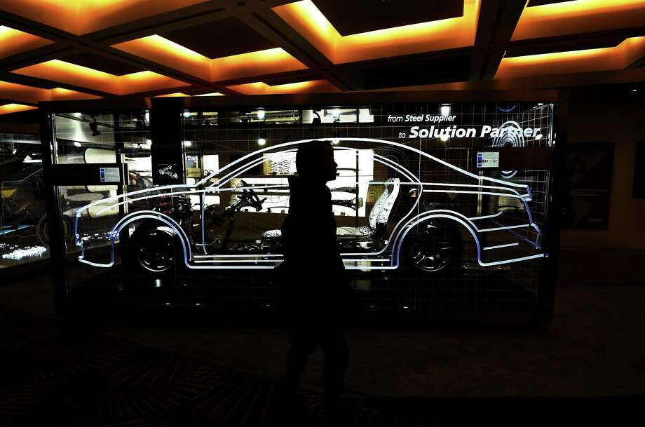 A woman walks past a booth as preparations are underway for the 2016 North American International Auto Show in Detroit. Photo: Jewel Samad /AFP / Getty Images / AFP