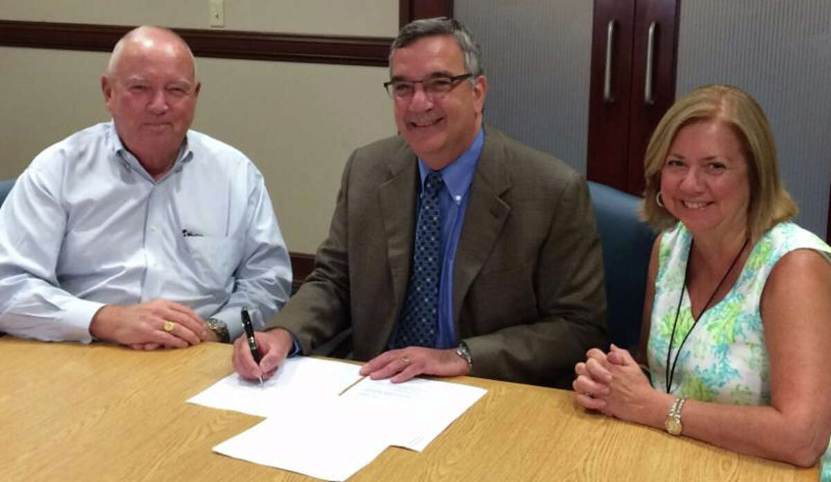 Al Barber, president, Catholic Charities of Fairfield County; Dr. Stuart G. Marcus, president and CEO, St. Vincent's Health Services; and Peggy Hardy, vice president, behavioral health, St. Vincent's MultiSpecialty Group sign the paperwork making this collaboration official.