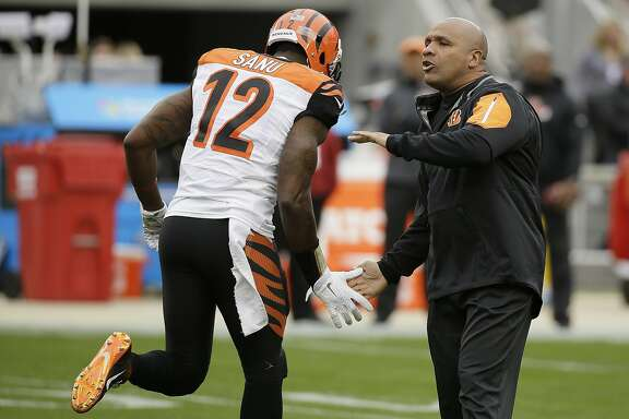 Cincinnati Bengals offensive coordinator Hue Jackson, right, greets wide receiver Mohamed Sanu (12) before an NFL football game against the San Francisco 49ers in Santa Clara, Calif., Sunday, Dec. 20, 2015. (AP Photo/Eric Risberg)