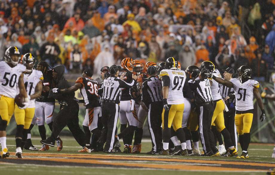 Officials step in between players from Cincinnati Bengals and Pittsburgh Steelers and try to sort everything out near the end of an NFL wild-card playoff football game Saturday. Photo: Gary Landers, Associated Press