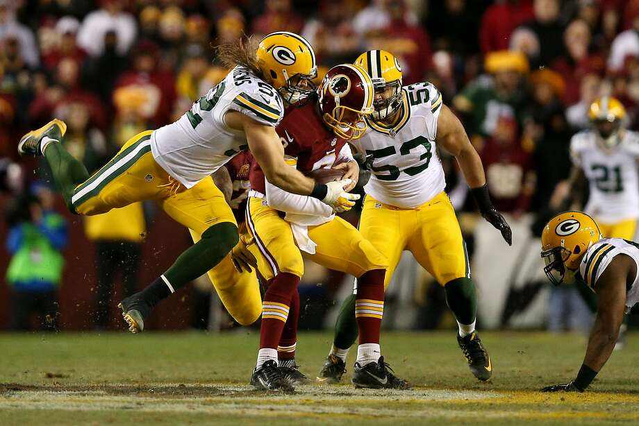 Green Bay's Clay Matthews wraps up Washington's Kirk Cousins, who was sacked six times. Photo: Patrick Smith, Getty Images