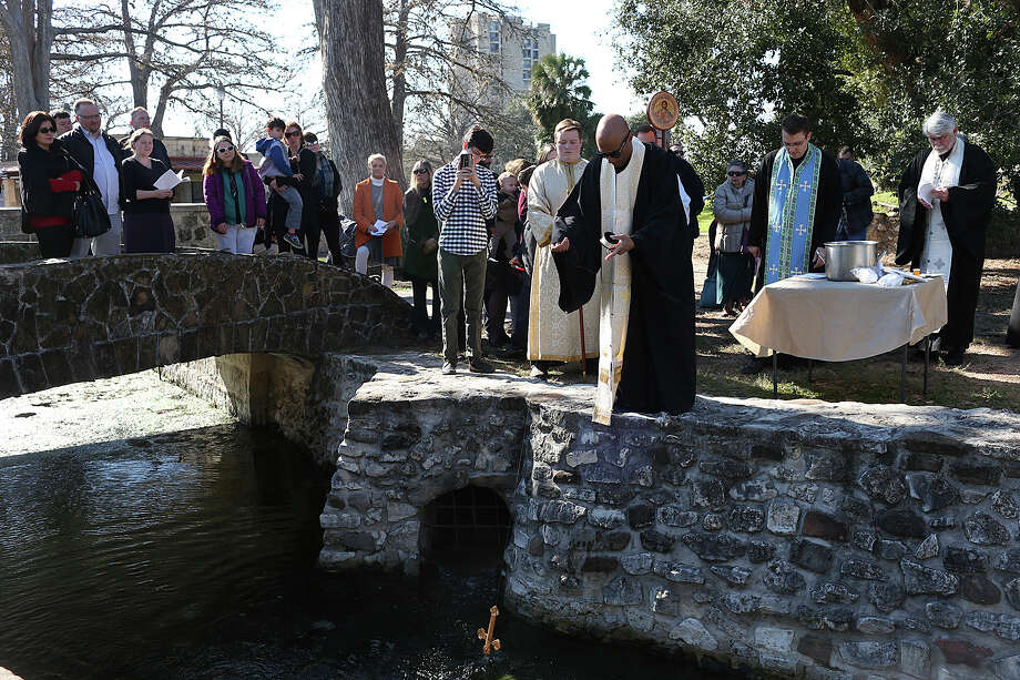 U.S. Air Force Chaplain Father Joseph Gardner, a colonel stationed at Joint Base San Antonio-:Lackland, throws a crucifix into the water as members of the Orthodox Christian community gather for an Outdoor Great Blessing of the waters at the San Pedro Springs, Sunday, Jan. 10, 2016. Congregants from St. Antony the Great Orthodox Church, St. Ephraim Orthodox Church and St. Sophia's Greek Orthodox Church gathered for the yearly event that was held for the first time at the headwaters of San Pedro Creek. In Orthodox custom, the Feast of the Theophany (the revelation of Christ through his baptism by St. John the Baptist) is celebrated on Jan. 6 with the blessing of waters - holy water for church use and the blessing of water sources such as lakes, rivers and oceans. Photo: Jerry Lara, Staff / San Antonio Express-News / © 2016 San Antonio Express-News