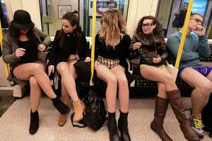 "Participants in the annual International ""No Pants Subway Ride"" travel on a London underground train in London, on January 10, 2016. Started in 2002 with only seven participants, the day is now marked in over 60 cities around the world. The idea behind ""No Pants"" is that random passengers board a subway car at separate stops in the middle of winter, without wearing trousers. The participants wear all of the usual winter clothing on their top half such as hats, scarves and gloves and do not acknowledge each other's similar state of undress.   AFP PHOTO / LEON NEAL / AFP / LEON NEAL"