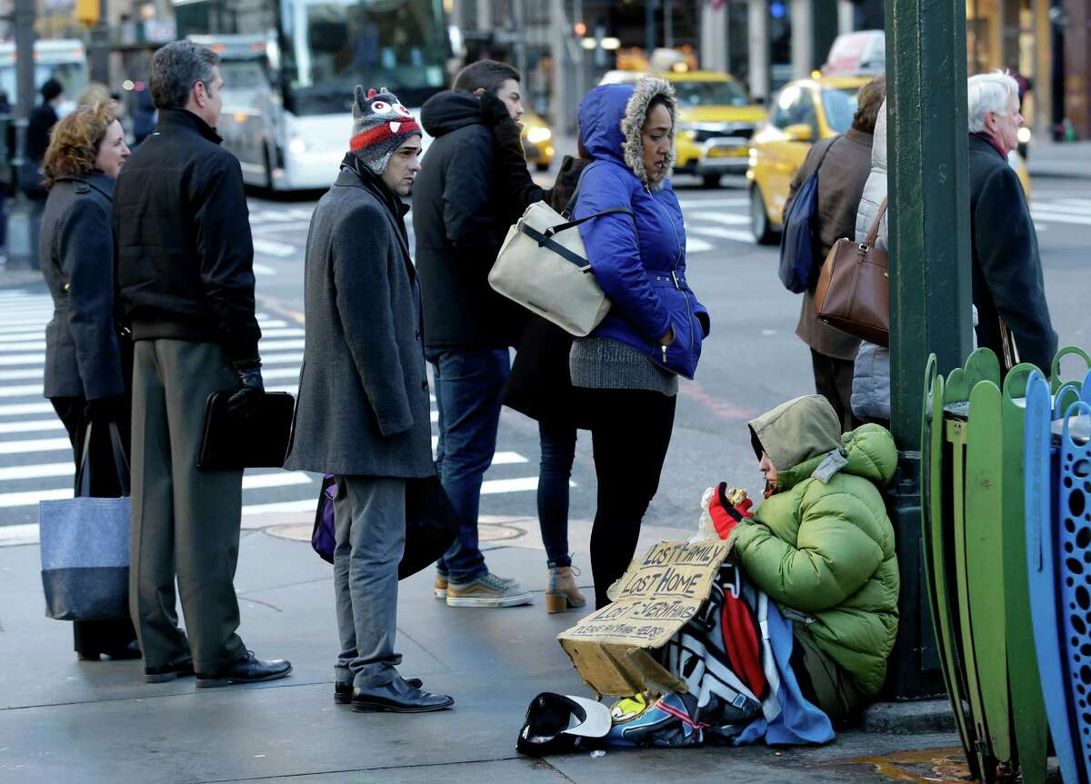 FILE - In this Jan. 5, 2016, file photo, a homeless woman, who only wanted to be identified as Lala, asks for money on a street corner in midtown Manhattan in New York. As bitter winter weather arrived in the Northeast, New York Gov. Andrew Cuomo issued an executive order requiring the homeless to be forcibly removed from the streets in freezing temperatures. The Associated Press spoke to about three dozen people living on the city's streets about how, or even if, new policies on the homeless announced by Cuomo and New York Mayor Bill de Blasio are affecting them. (AP Photo/Seth Wenig, File) ORG XMIT: NYR201
