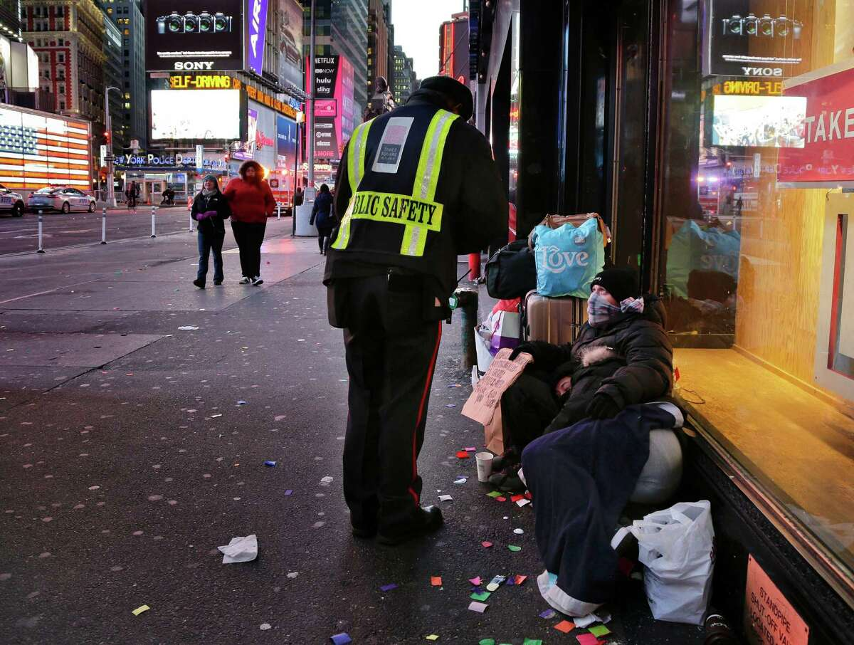 In this Jan. 4, 2016, file photo, a public safety officer talks to a homeless couple in New York's Times Square. As bitter winter temperatures arrived in the northeast, New York?'s Gov. Mario Cuomo issued an executive order requiring the homeless to be forcibly removed from the street in freezing weather. The Associated Press spoke to about three dozen people living on the city's streets about how, or even if, new policies on the homeless announced by Cuomo and New York Mayor Bill de Blasio are affecting them. (AP Photo/Julie Jacobson, File) ORG XMIT: NYR202
