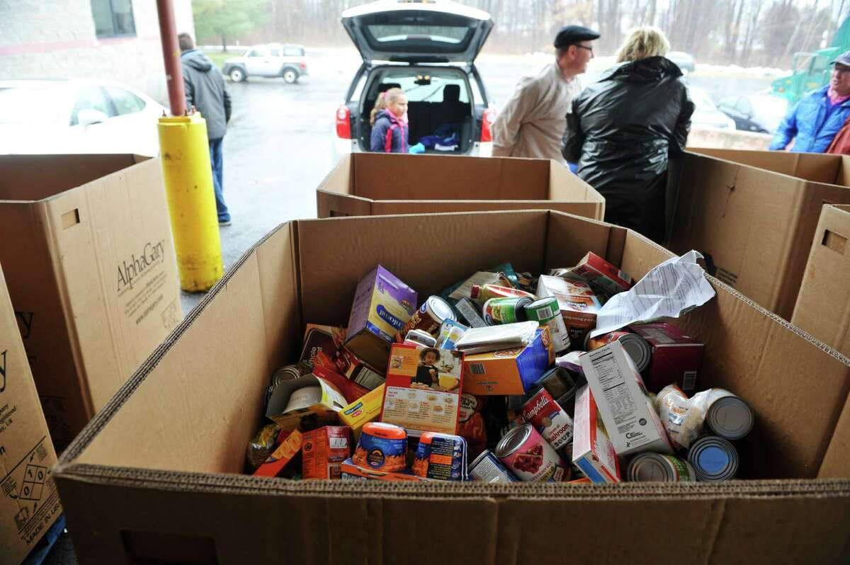 Volunteers and staff with the Regional Food Bank of Northeastern New York unload donated food during the 9th Annual Neighborhood Food Drive on Sunday, Jan. 10, 2016, in Latham, N.Y. Volunteers delivered 12,100 bags with a preprinted letter of explanation in targeted neighborhoods requesting non-perishable food donations, which were collected on Sunday and brought to the food bank. Last year, over 32,000 pounds of food was collected over the weekend, enough for 25,000 meals. (Paul Buckowski / Times Union)