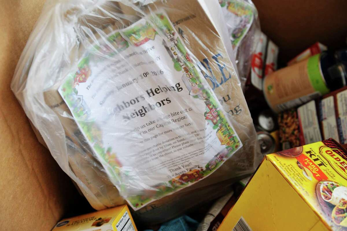 A bag of food warped in plastic to protect it from the rain is seen in one of the collection bins as volunteers and staff with the Regional Food Bank of Northeastern New York unload donated food during the 9th Annual Neighborhood Food Drive on Sunday, Jan. 10, 2016, in Latham, N.Y. Volunteers delivered 12,100 bags with a preprinted letter of explanation in targeted neighborhoods requesting non-perishable food donations, which were collected on Sunday and brought to the food bank. Last year, over 32,000 pounds of food was collected over the weekend, enough for 25,000 meals. (Paul Buckowski / Times Union)