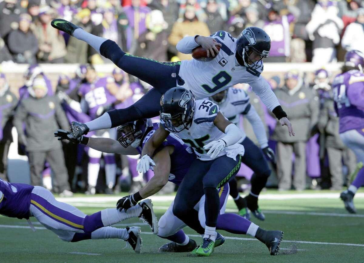 Seattle Seahawks punter Jon Ryan (9) jumps over Minnesota Vikings linebacker Casey Matthews (59) as he runs the ball during the first half of an NFL wild-card football game against the Minnesota Vikings, Sunday, Jan. 10, 2016, in Minneapolis. (AP Photo/Nam Y. Huh) ORG XMIT: MNKS127