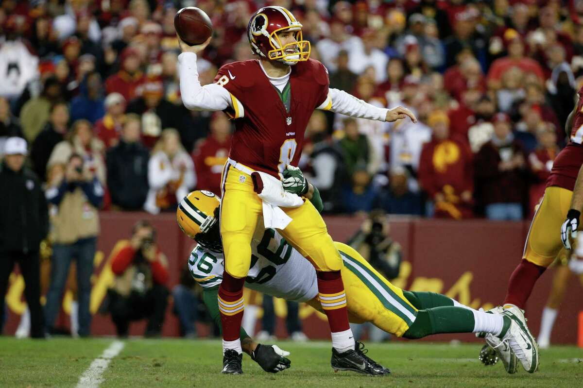 Washington Redskins quarterback Kirk Cousins (8) throws the ball under pressure from Green Bay Packers outside linebacker Julius Peppers (56) during the first half of an NFL wild card playoff football game in Landover, Md., Sunday, Jan. 10, 2016. (AP Photo/Alex Brandon) ORG XMIT: FDX112
