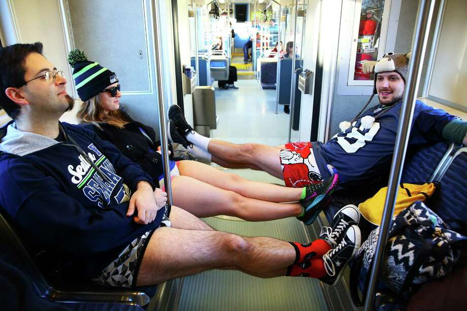Joe Flanik (left), Laura Brinkmann, and Zach Roberts ride pants-less during Seattle's annual No Pants Light Rail Ride. Participants stripped down to their underwear and rode the rail from Westlake Center to Seattle-Tacoma International Airport, as if nothing is unusual. Photographed on Sunday, January 10, 2016. Photo: GENNA MARTIN, SEATTLEPI.COM / SEATTLEPI.COM