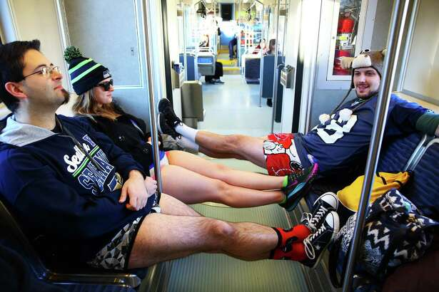 Joe Flanik (left), Laura Brinkmann, and Zach Roberts ride pants-less during Seattle's annual No Pants Light Rail Ride. Participants stripped down to their underwear and rode the rail from Westlake Center to Seattle-Tacoma International Airport, as if nothing is unusual. Photographed on Sunday, January 10, 2016.