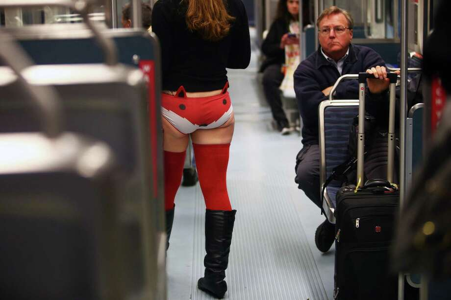 Other riders look on as Kendra Pedersen rides pants-less during Seattle's annual No Pants Light Rail Ride. Participants stripped down to their underwear and rode the rail from Westlake Center to Seattle-Tacoma International Airport, as if nothing is unusual. Photographed on Sunday, January 10, 2016. Photo: GENNA MARTIN, SEATTLEPI.COM / SEATTLEPI.COM