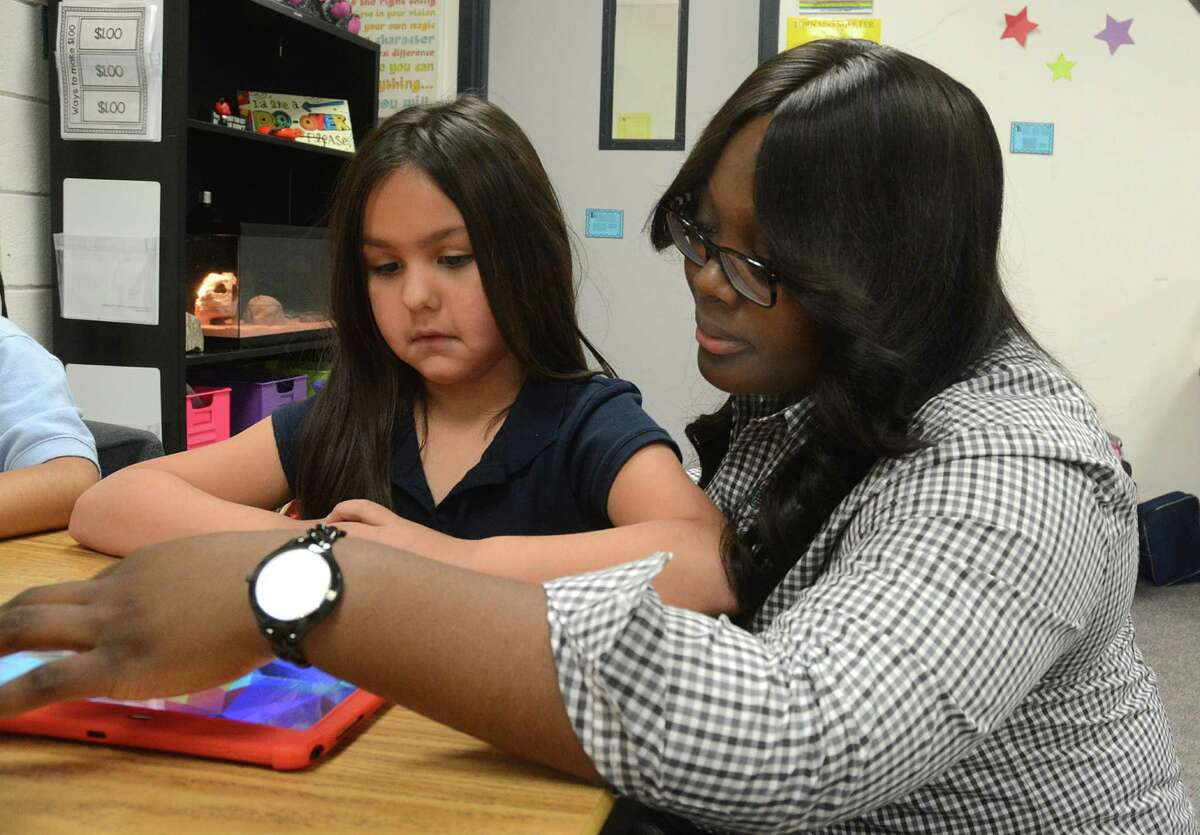 Second grade teacher Natalie Johnson helps Janessa Herrera set up her tablet for a math class. Johnson uses technology in her classroom at Beneke Elementary School, 3840 Briarchase Drive, to motivate her students.