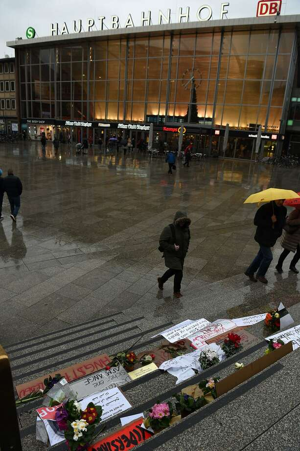 "People walk past flowers and letters of protest that are laid down on the steps in front of the Cologne main train station in Cologne, western Germany on January 11, 2016. German authorities said that nearly all the suspects in a rash of New Year's Eve violence against women in Cologne were ""of foreign origin"", as foreigners came under attack amid surging tensions. During a press conference, Ralf Jaeger, the interior minister of North Rhine-Westphalia state, released initial findings of a criminal probe over the crime spree and said that the attackers emerged from a group of more than 1,000 ""Arab and North African"" men who gathered between the main railway station and the city's iconic Gothic cathedral during the year-end festivities. / AFP / PATRIK STOLLARZPATRIK STOLLARZ/AFP/Getty Images Photo: Patrik Stollarz, AFP / Getty Images"