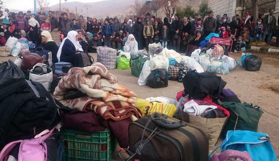 Syrians wait for trucks carrying critically needed food and medicine to arrive in the town of Madaya. Photo: Marwan Ibrahim, AFP / Getty Images