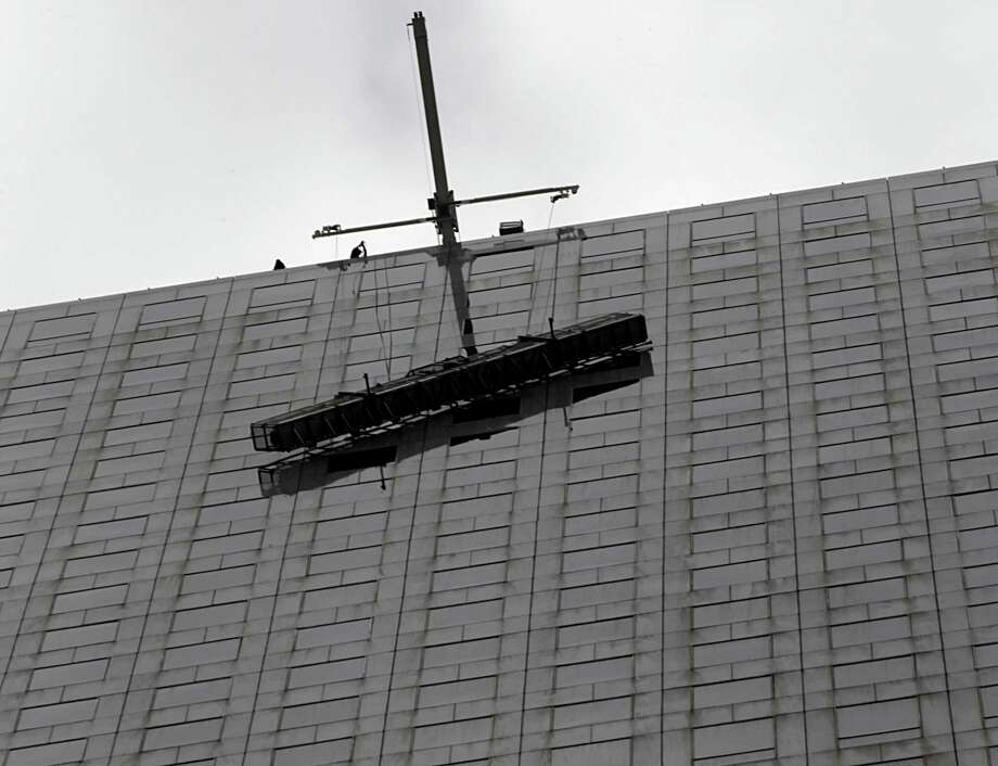 Houston Fire Department firefighters during a high rescue of window washer on the Chase Tower Monday, Jan. 11, 2016, in Houston. Photo: James Nielsen, Houston Chronicle / © 2015  Houston Chronicle