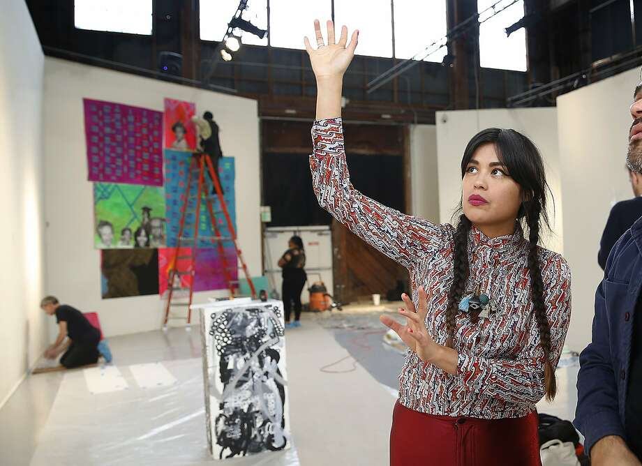 Grace Rosario Perkins, a Black Salt Collective artist, helps install members' works at SOMArts. Photo: Liz Hafalia, The Chronicle