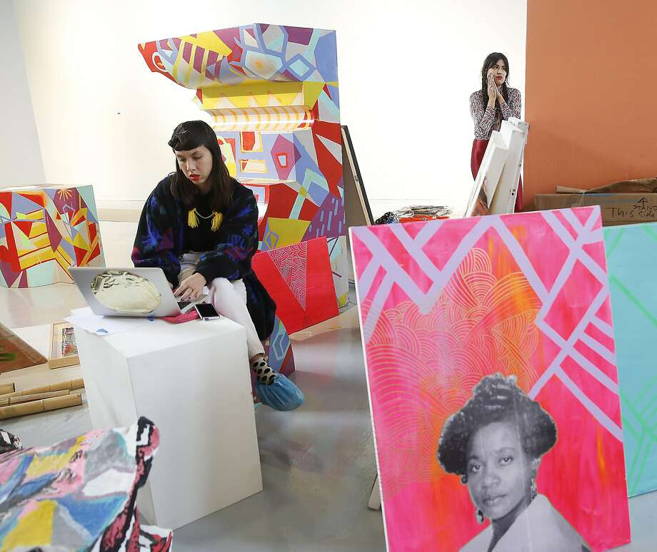 Founders and artists of Black Salt, a women's artist collective, Anna Luisa Petrisko (Jeepneys) seated at left, and Grace Rosario Perkins (background right) work on their show at SOMArts in San Francisco, California, on Friday,  January 8, 2015. Photo: Liz Hafalia, The Chronicle